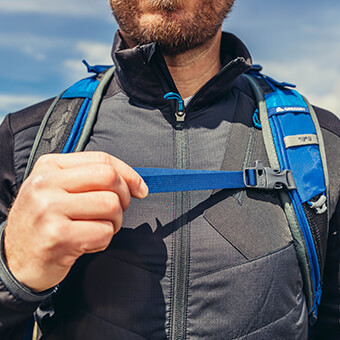 Perforated shoulder harness with sternum strap featuring integrated safety whistle
