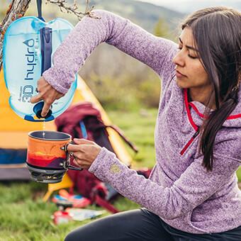 Basecamp Modus - Wasser auf Knopfdruck durch das spezielle Verschlusssystem und integrierte Aufhängung, um die Trinkblase überall zu befestigen.